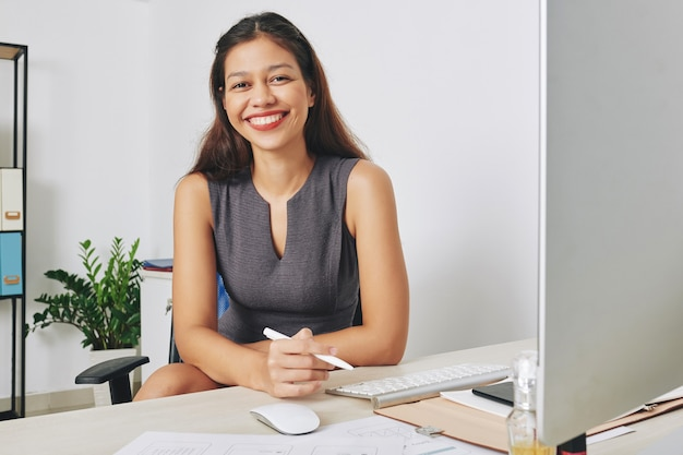 Portret młodej uśmiechniętej projektantki interfejsu użytkownika pracującej na komputerze przy biurku i szkicując projekt nowej aplikacji mobilnej