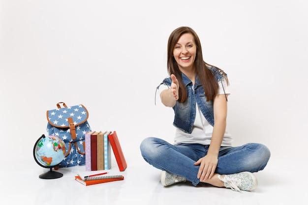 Portret młodej uśmiechniętej studentki dorywczo siedzącej z wyciągniętą ręką na powitanie w pobliżu kuli ziemskiej, plecaka, podręczników szkolnych na białym tle