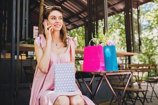 Portret młodej uśmiechniętej szczęśliwej atrakcyjnej kobiety siedzącej w kawiarni rozmawiając przez telefon z torby na zakupy, letni strój moda, styl hipster, różowa bawełniana sukienka, modna odzież