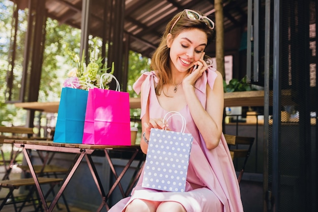 Portret młodej uśmiechniętej szczęśliwej atrakcyjnej kobiety siedzącej w kawiarni rozmawiającej na telefonie z torbami na zakupy