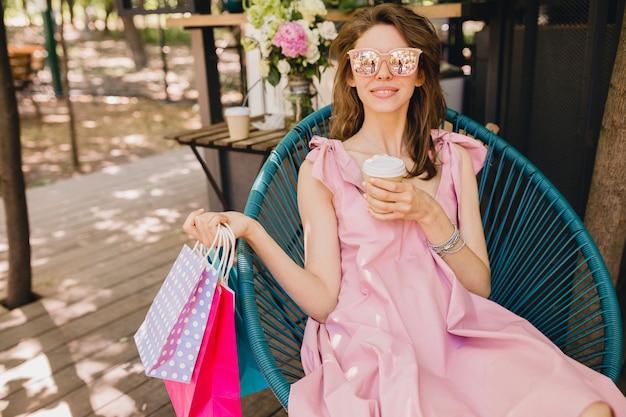 Portret młodej uśmiechniętej szczęśliwej atrakcyjnej kobiety siedzącej w kawiarni z torbami na zakupy pijącej kawę, letni strój modowy, różowa bawełniana sukienka, modna odzież