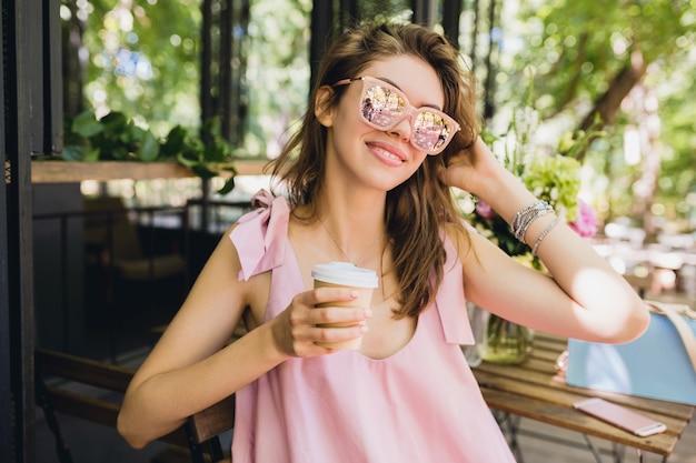 Portret młodej uśmiechniętej szczęśliwej ładnej kobiety siedzącej w kawiarni pijąc kawę, letni strój moda, różowa bawełniana sukienka, modne dodatki odzieżowe