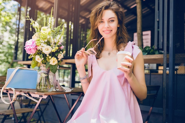 Portret młodej uśmiechniętej szczęśliwej ładnej kobiety siedzącej w kawiarni pijącej kawę