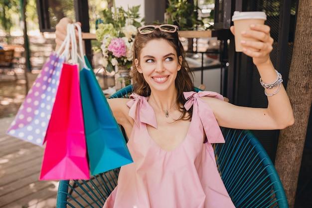 Portret młodej uśmiechniętej szczęśliwej ładnej kobiety z podekscytowanym wyrazem twarzy siedzi w kawiarni z torby na zakupy pijąc kawę, letni strój modowy, styl hipster, różowa bawełniana sukienka, modna odzież