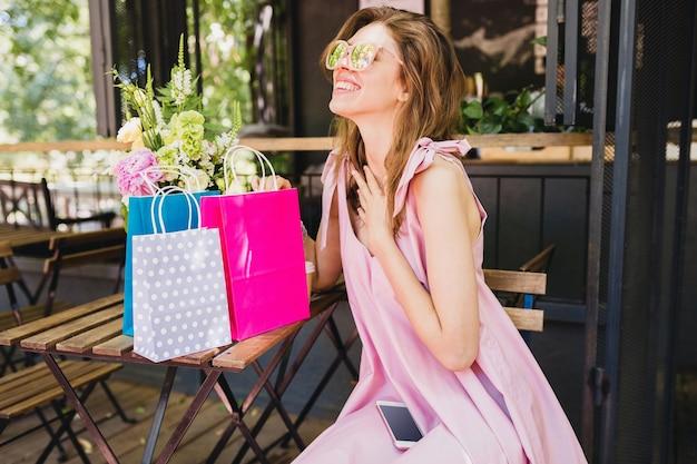 Portret młodej uśmiechniętej szczęśliwej ładnej kobiety z wyrazem zdziwionej twarzy siedzącej w kawiarni z torbami na zakupy