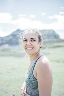 Portret młodej uśmiechniętej twarzy kobiety częściowo pokrytej rozwianymi włosami w wietrzny dzień stojącej na górze - beztroska kobieta