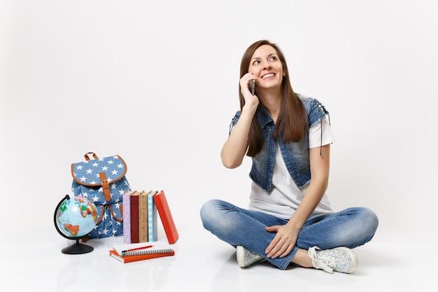 Portret młodej uśmiechniętej zamyślonej studentki rozmawiającej przez telefon komórkowy, patrząc w górę, siedzącej w pobliżu kuli ziemskiej, plecaka, podręczników szkolnych na białym tle
