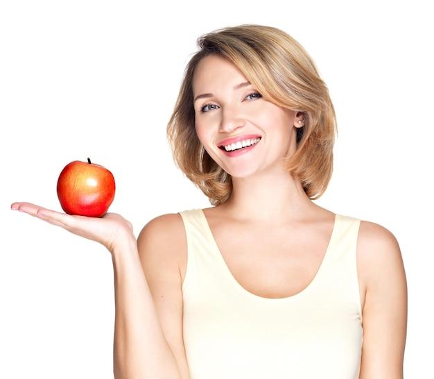 Portret młodej uśmiechniętej zdrowej kobiety z czerwonym jabłkiem - na białym tle.