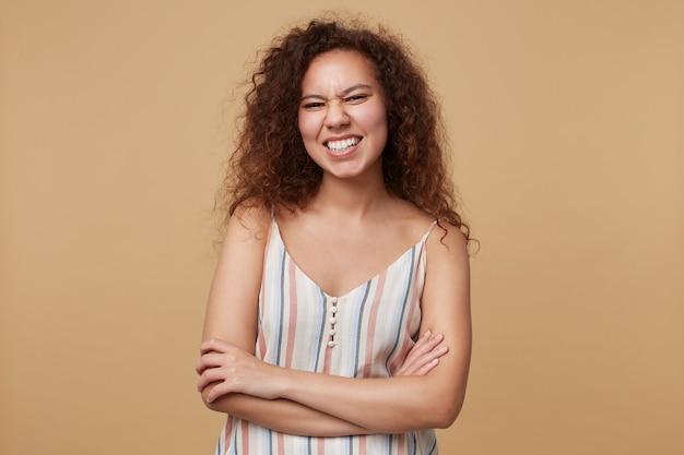 Portret młodej wesołej brązowowłosej kręconej kobiety marszczącej brwi, uśmiechającej się szeroko i krzyżującej ręce na piersi, pozującej na beżu