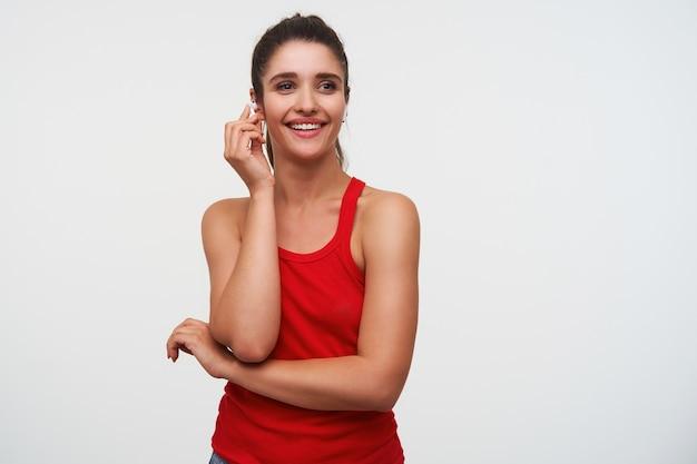 Portret młodej wesołej brunetki pani ubrana w czerwoną koszulkę, patrzy w kamerę i szeroko się uśmiecha, w słuchawkach, stoi na białym tle.