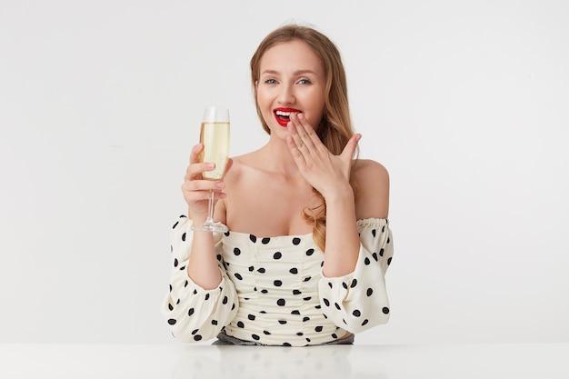 Portret młodej wesołej dziewczyny o długich blond włosach, z czerwonymi ustami w sukience w kropki, podnoszącej kieliszek szampana, śmieje się i zakrywa usta ręką odizolowaną na białym tle.