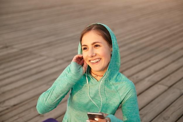 Portret młodej wesołej dziewczyny w jasnej odzieży sportowej, cieszyć się zachodem słońca, rozmawiając z przyjaciółmi na słuchawkach po porannej jodze, uśmiechając się i odwracając wzrok.