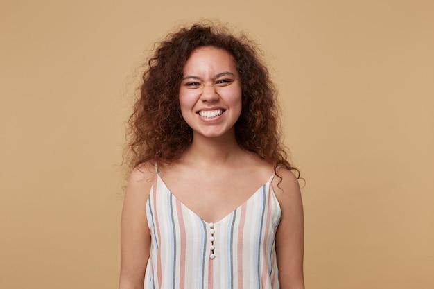 Portret młodej wesołej kręconej brunetki kobiety z przypadkową fryzurą, pokazując jej białe idealne zęby, śmiejąc się radośnie, odizolowane na beżu