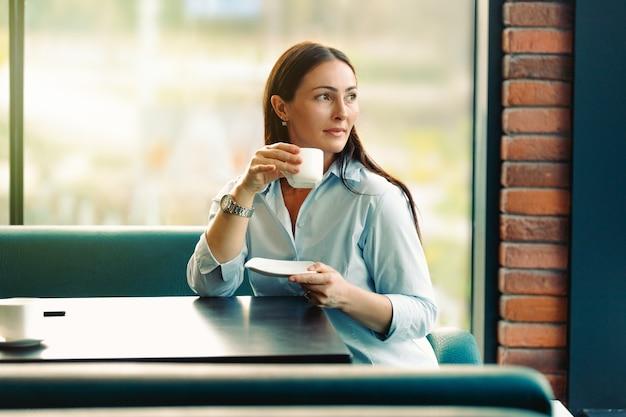 Portret młodej wspaniałej kobiety picia herbaty i patrząc z uśmiechem, ciesząc się wolnym czasem, miła biznesowa kobieta w nowoczesnej kawiarni podczas przerwy w pracy.