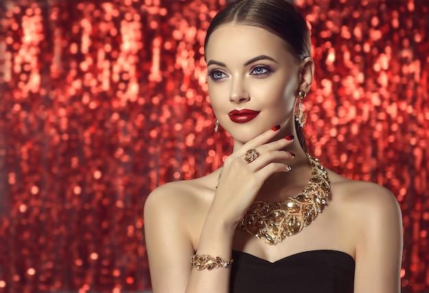 Portret młodej wspaniałej kobiety ubranej w zestaw biżuterii - naszyjnik, pierścionek, bransoletka i kolczyki. niebieskooka modelka demonstruje atrakcyjny makijaż i manicure na błyszczącym czerwonym tle.
