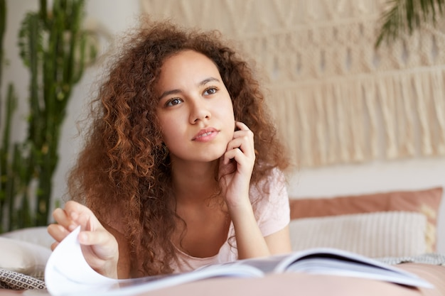 Portret młodej, wypoczętej afroamerykanki dziewczyny z kręconymi włosami, uspokojony patrzy w kamerę i dotyka brody, leży na łóżku i czyta nowy numer magazynu.
