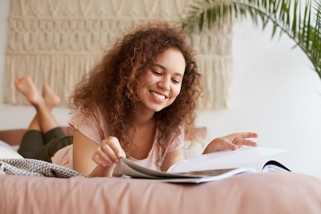 Portret młodej, wypoczętej, pozytywnej afroamerykanki z kręconymi włosami, leży na łóżku i cieszy się wolnym dniem, szeroko się uśmiecha i wygląda na szczęśliwą, czyta nowy numer ulubionego magazynu.