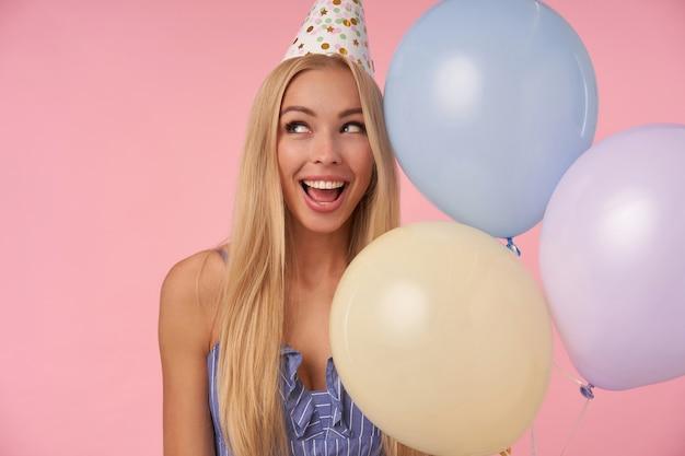 Portret młodej zachwyconej kobiety z długimi blond włosami pozuje w wielobarwnych balonach, świętuje wakacje, raduje się z miłej imprezy razem z przyjaciółmi, stojąc na różowym tle