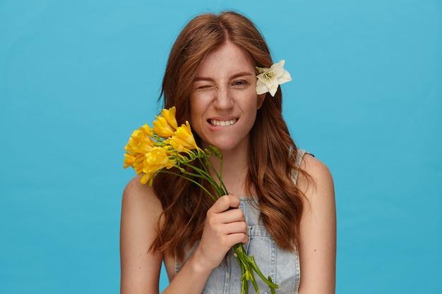 Portret młodej zalotnej damy z falującą fryzurą trzymającą bukiet kwiatów i gryzącą dolną wargę, patrząc żartobliwie na aparat, odizolowany na niebieskim tle