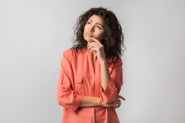 Portret młodej zamyślonej brunetki kobiety w pomarańczowej koszuli, kręcone włosy, letni styl, sfrustrowany wyraz twarzy, smutne emocje, odwrócenie wzroku, myślenie, problem, pomysł, rasa mieszana, odizolowany
