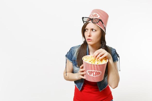 Portret młodej zaniepokojonej atrakcyjnej kobiety w okularach 3d z wiadrem na popcorn na głowie oglądając film filmowy, jedzący popcorn z wiadra na białym tle. emocje w koncepcji kina.