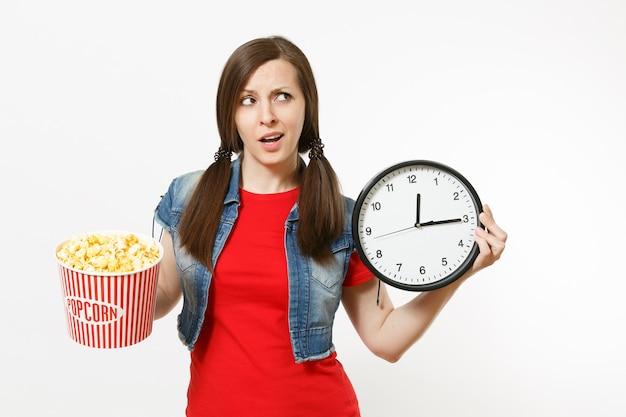 Portret młodej zaniepokojonej kobiety w zwykłych ubraniach oglądając film filmowy, trzymając wiadro popcornu i budzik, patrząc na bok na przestrzeni kopii na białym tle. emocje w koncepcji kina