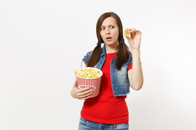 Portret młodej zaniepokojonej ładnej brunetki kobiety w zwykłych ubraniach, oglądającej film, trzymając w ręku wiadro popcornu i złotego bitcoina na białym tle. emocje w koncepcji kina.