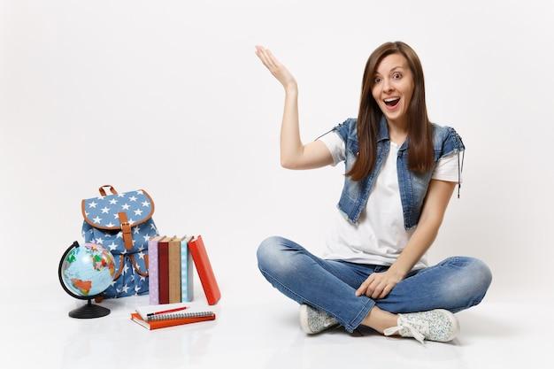 Portret młodej zaskoczonej studentki w dżinsowych ubraniach, wskazującej rękę na bok, siedzącej w pobliżu kuli ziemskiej, plecaka, podręczników szkolnych na białym tle