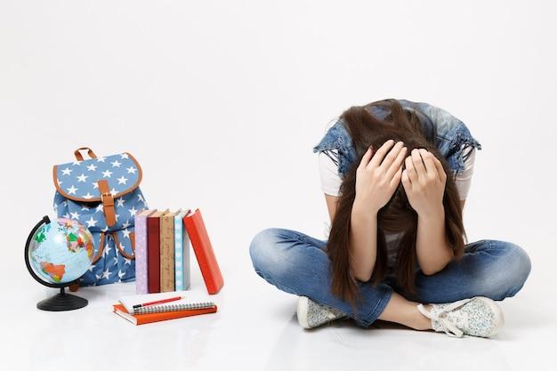 Portret młodej zdenerwowanej depresyjnej studentki pochylającej się przywiązanie do głowy, siedzącej patrzącej na kulę ziemską, plecak, podręczniki szkolne na białym tle