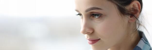 Portret młodej zdenerwowanej kobiety w pobliżu depresji okiennej i koncepcji chronicznego zmęczenia