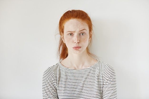 Portret młodej zdenerwowanej kobiety z piegami i ściągniętymi ustami o rozczarowanym, nieszczęśliwym spojrzeniu, marszcząca brwi i dąsająca się. uparta nastolatka wyglądająca na złą lub zirytowaną.