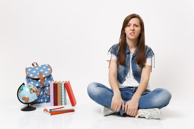 Portret młodej zdziwionej studentki w dżinsowych ubraniach gryzących usta i siedzącej w pobliżu kuli ziemskiej, plecaka, podręczników szkolnych na białym tle