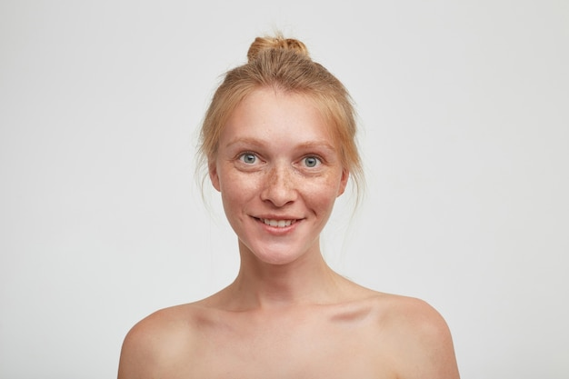 Portret młodej zielonookiej rudowłosej kobiety z naturalnym makijażem wyglądającej pozytywnie i uśmiechającej się wesoło, odizolowanej na białej ścianie z nagimi ramionami