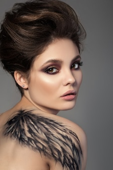 Portret młodej zmysłowej kobiety brunetka z czarnym skrzydłem bodyart na plecach