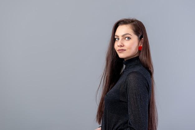 Portret młodej zmysłowej kobiety z długimi włosami na szarym tle z kopią przestrzeni