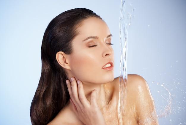 Portret młodej zmysłowości pięknej kobiety pod strumieniem wody - niebieskie tło