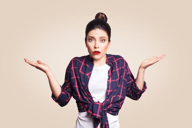 Portret młodej zszokowanej brunetki w stylu casual, patrzącej desperacko lub w panice, trzymając otwarte usta i robiąc bezradny gest rękami, nie wie, co robić.