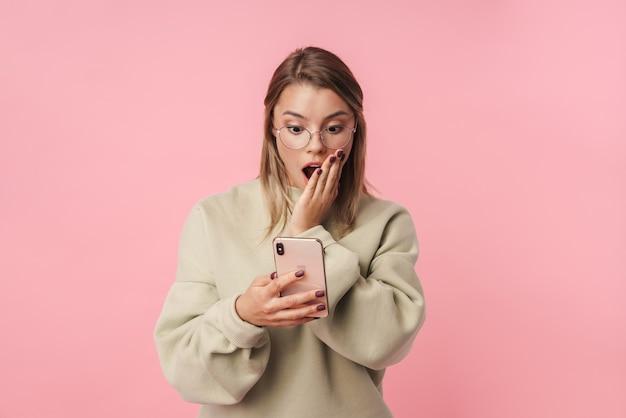Portret młodej zszokowanej kobiety w okularach przy użyciu telefonu komórkowego izolowanego nad różową ścianą