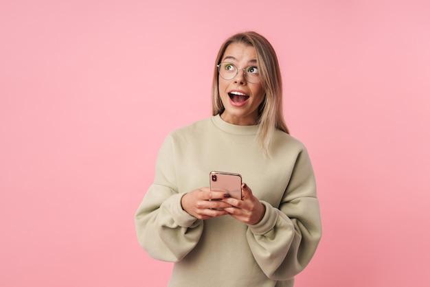 Portret młodej zszokowanej kobiety w okularach, używającej telefonu komórkowego i patrzącej w górę, odizolowanej na różowej ścianie