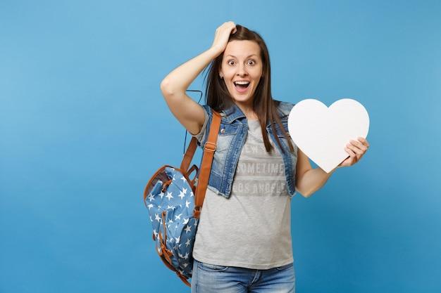Portret młodej zszokowanej podekscytowanej studentki z plecakiem trzymającej białe serce z miejsca na kopię i przywiązanie do głowy na białym tle na niebieskim tle. edukacja na studiach. skopiuj miejsce na reklamę.