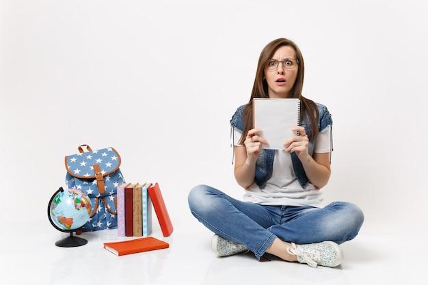 Portret młodej zszokowanej przestraszonej studentki w okularach trzymającej ołówek, notebooka siedzącego w pobliżu kuli ziemskiej, plecaka, podręczników szkolnych na białym tle