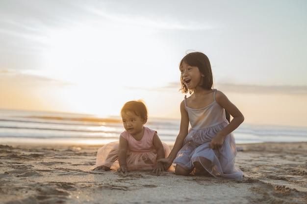 Portret młodszych sióstr, ciesząc się wakacjami na plaży