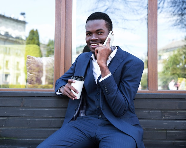 Portret młody afrykański biznesmen opowiada na telefonie komórkowym