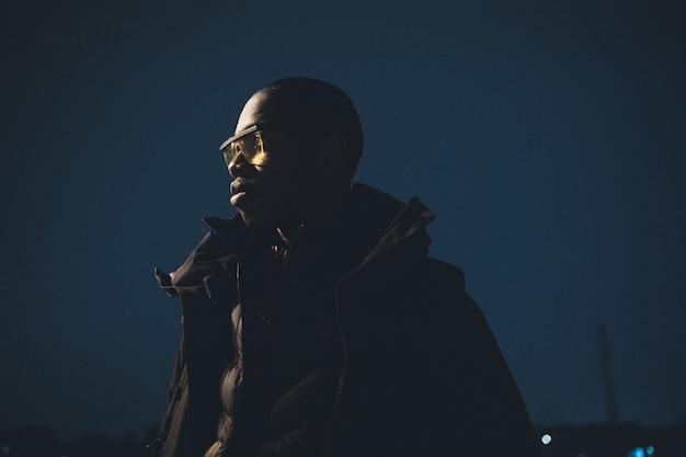 Portret młody afrykański mężczyzna pozować plenerowy i patrzeć dalej