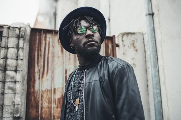 Portret młody afrykański mężczyzna pozycja w ulicie i patrzeć dalej