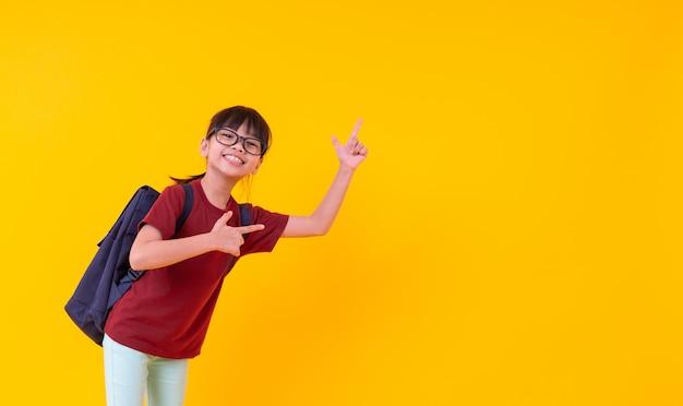 Portret młody azjatycki dziewczyna uczeń wskazuje up na kolorze żółtym