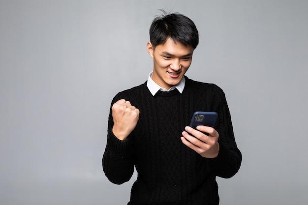 Portret młody azjatycki mężczyzna patrzeje szczęśliwy podczas gdy czytający dobre wieści na smartphone na biel ścianie