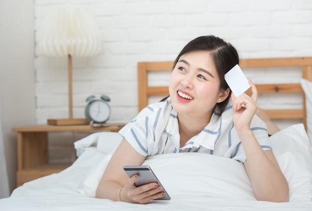 Portret młody azjatykci kobiety lying on the beach na łóżku używać cyfrowego mądrze telefon komórkowego