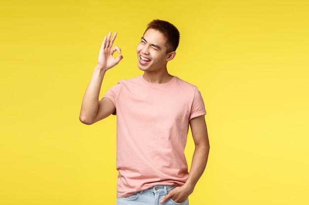 Portret młody azjatykci mężczyzna seansu gest nad kolor żółty ścianą