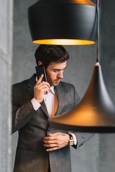 Portret młody biznesmen opowiada na smartphone z breloczka światłem w przedpolu
